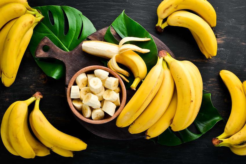 Banany obrane ze skórki i nieobrane leżą na ciemnym blacie, banany w diecie, ile bananów można jeść podczas stosowania diety bananowej i jakie są efekty diety bananowej