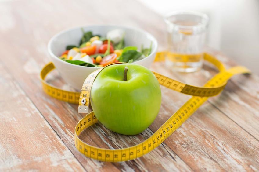 Na blacie leży zielone jabłko, miarka oraz miska z warzywami, efekty stosowania diety jabłkowej, czy dieta jabłkowa jest dobra na żołądek