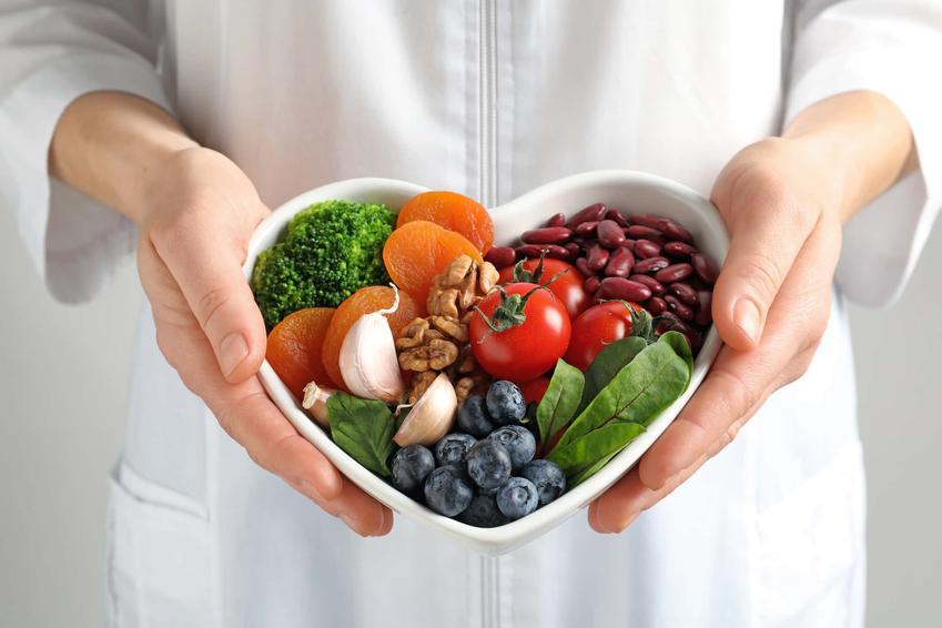 Kobiece dłonie trzymają misę w kształcie serca wypełnioną warzywami i owocami, czego unikać w jadłospisie w przypadku obecności bakterii helicobacter pylori, zakazane produkty a bakteria helicobacter pylori