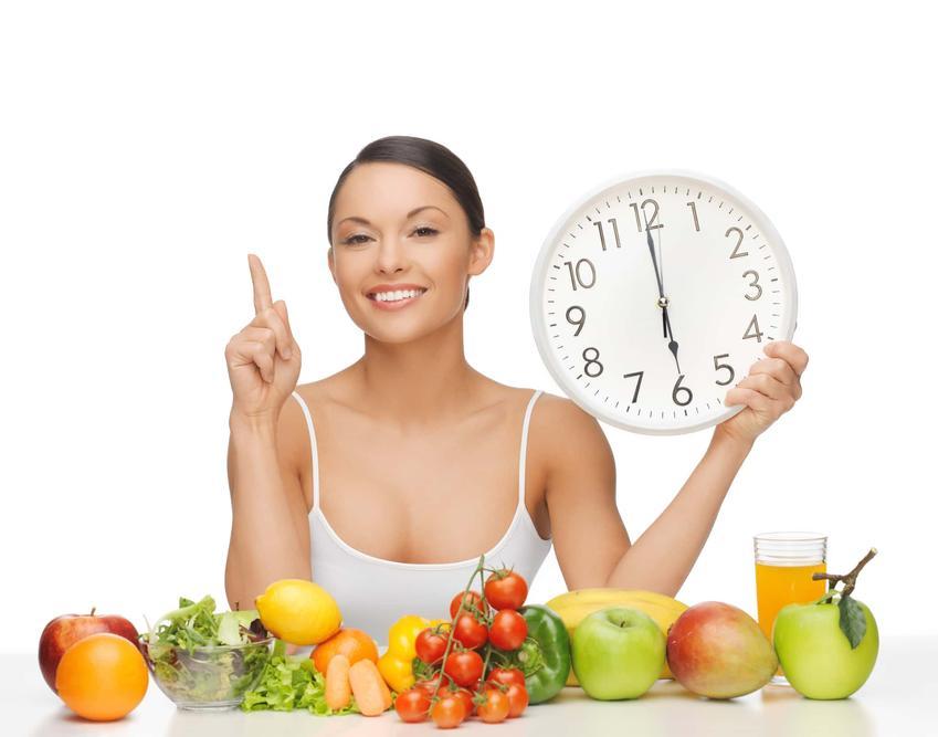 Kobieta otoczona warzywami i owocami w ręku trzyma zegar, kobieta na diecie okinkowej, efekty stosowania kiedy okienkowej i opinie na temat diety okienkowej