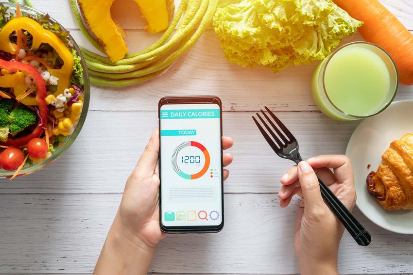 Dłoń trzyma telefon w ręku, naktórym jest grafika 1200 kcal, wokół stoi zdrowe jedzenie, zdrowe odżywianie przy diecie 1200 kcal, czego unikać w diecie niskokalorycznej