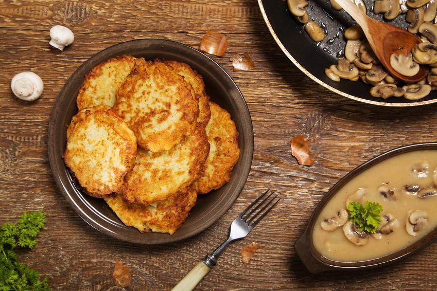 Placki ziemniaczane z sosem pieczarkowym na drewnianym stole, a także przepisy i wskazówki kulinarne