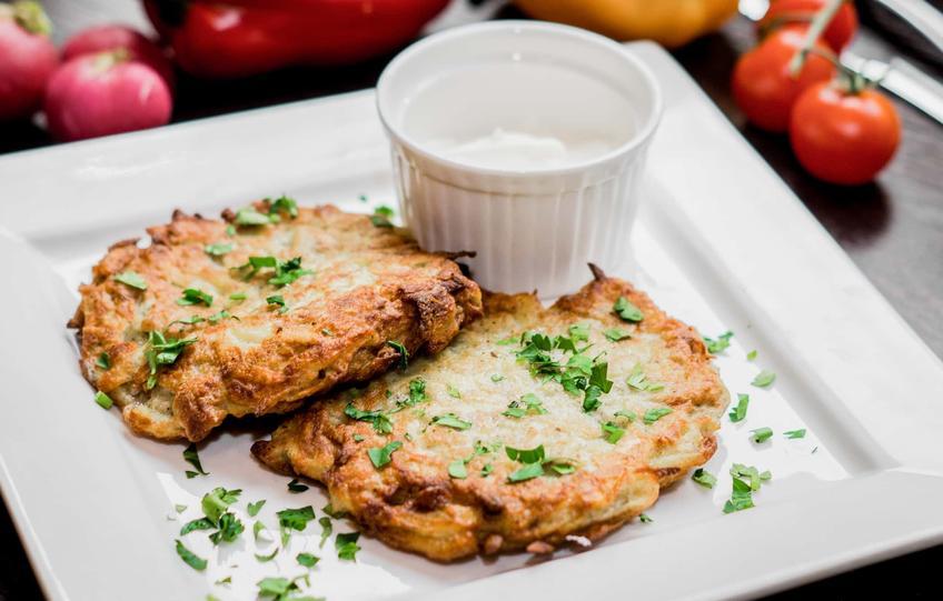 Pieczone placki ziemniaczane na talerzu z sosem śmietanowym oraz przepisy na placki ziemniaczane z piekarnika