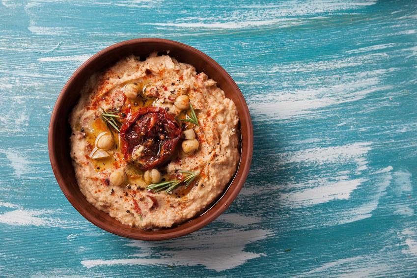 Hummus z suszonymi pomidorami w brązowej miseczce, a także ciekawe przepisy na nietypowy i smaczny hummus