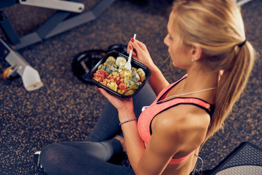 Kobieta jedząca posiłek potreningowy na siłowni, a także dieta na masę, najlepsze przepisy, skuteczność oraz zasady