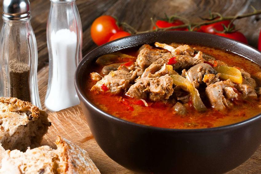 Zupa forszmak znajduje się w czarnej misce. Obok stoją pojemniki na sól i pieprz oraz leżą pomidory i przepołowiona bułka.