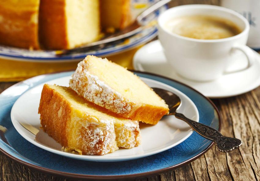 Babka cytrynowa znajduje się na białym talerzyku. Obok leży łyżeczka oraz stoi filiżanka z kawą. Widać talerz z resztą ciasta.