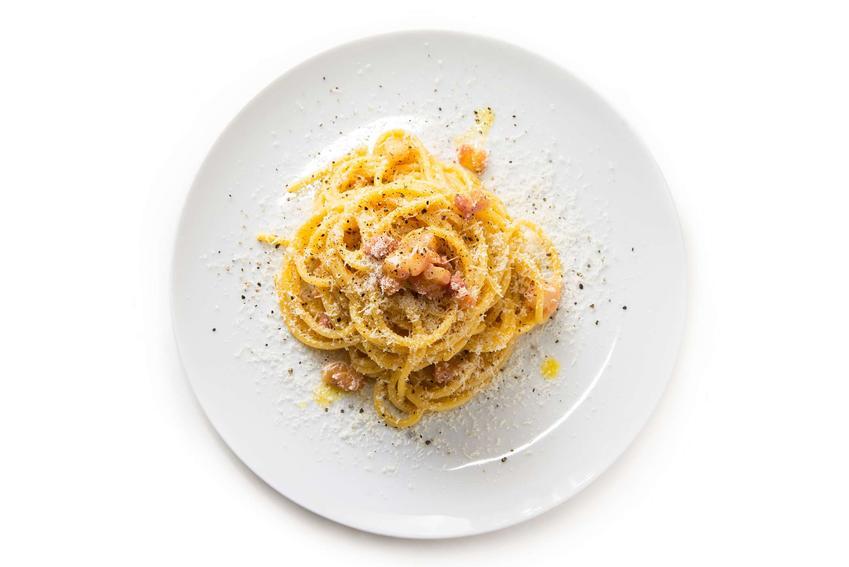 Spaghetti carbonara podane na eleganckim białym talerzu posypane serem i pieprzem.