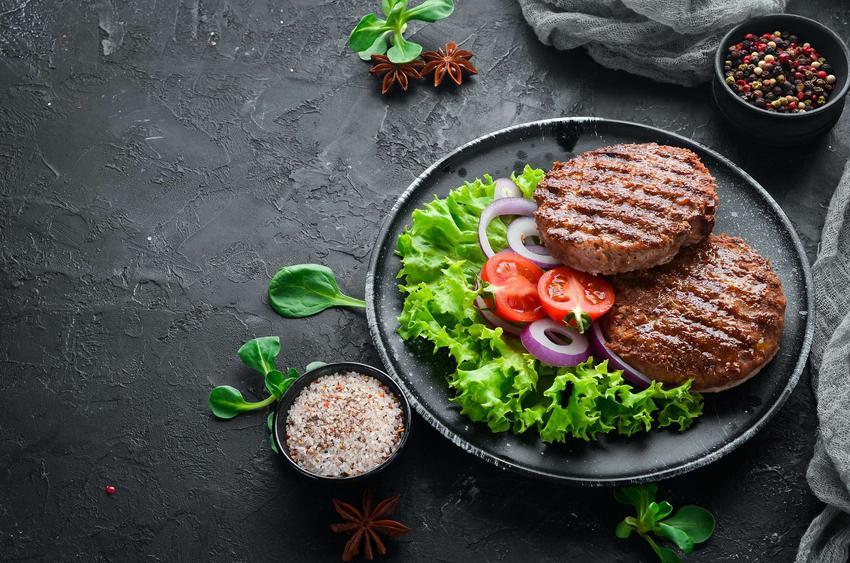 Burgery na czarnym talerzu podane z surowymi warzywami.