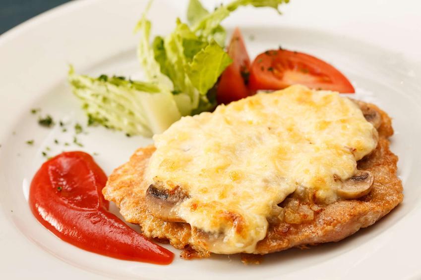 Schabowy z pieczarkami i serem na białym talerzu. Obok kotleta znajduje się ketchup oraz świeże warzywa.