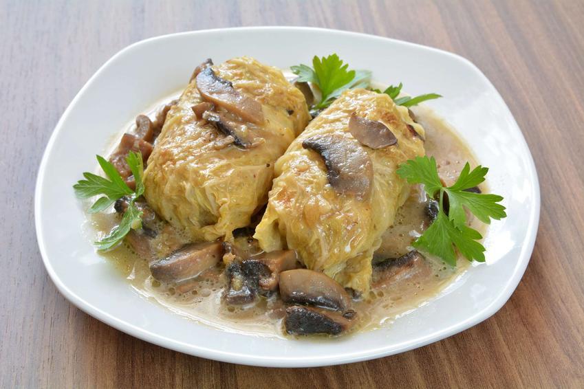 2 gołąbki w sosie pieczarkowym podane na białym talerzu i ozdobione listkami natki pietruszki