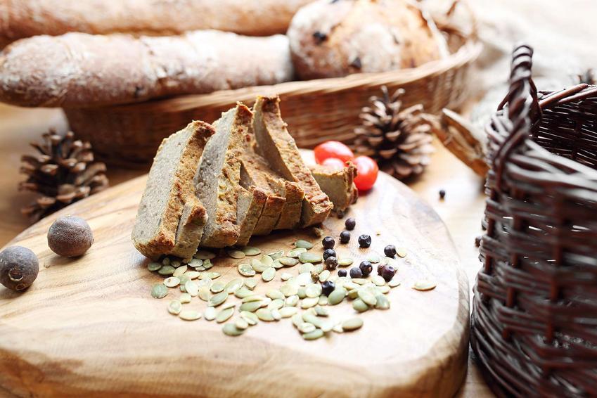 Pasztet z zająca podany na kawałku drewna, z pestkami, jałowce, zielem angielskim, z tyłu szyszki i kosz z pieczywem.