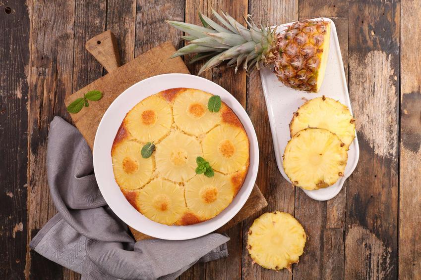 Ciasto z ananasem podane na białym talerzu, na drewnianej desce, obok szara ściereczka i pokrojony świeży ananas, na drewnianym blacie