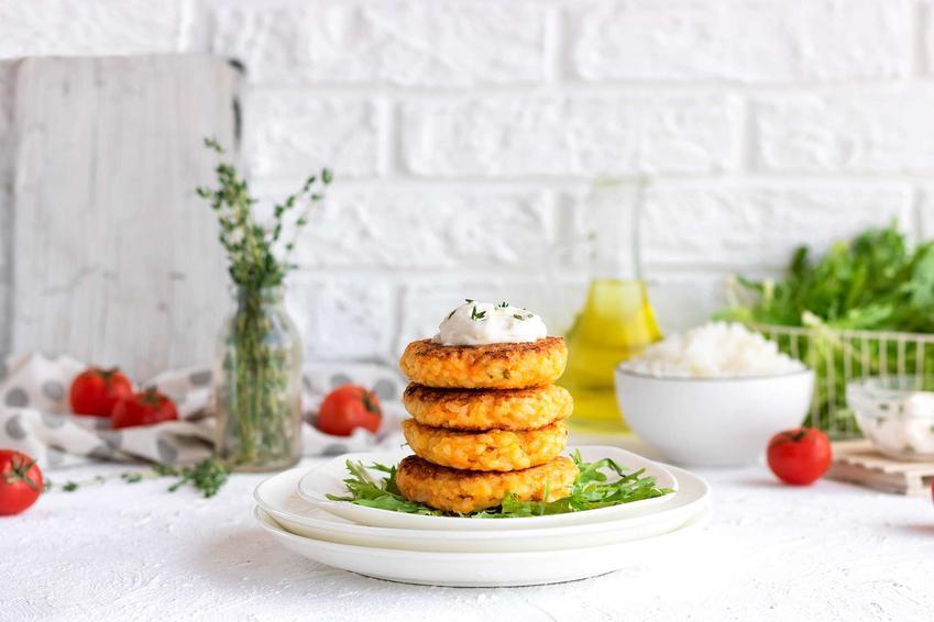 Kotlety wegetariańskie ułożone na białym talerzu z dodatkiem sosu. W tle pomidorki, miska z sosem, sałata, wazonik z roślinami.