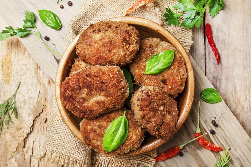 Kotlety wołowe podane w misce na drewnianej desce, obok świeże listki ziół, papryczki chili, na drewnianym stole