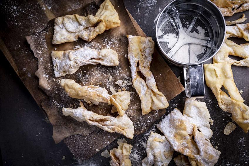 Faworki oprószone cukrem pudrem, podane na drewnianej desce.