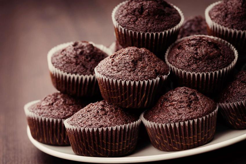 Muffinki czekoladowe są ułożone warstwowo na białym talerzu.