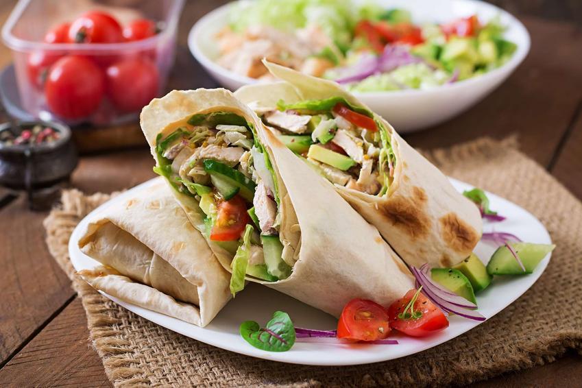 Tortilla ułożona na talerzyku ze świeżymi warzywami.
