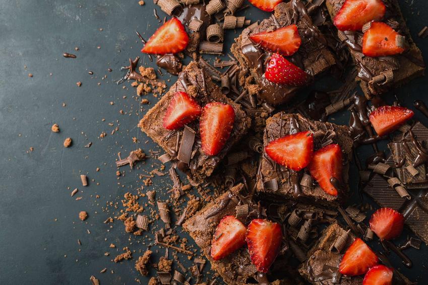 Brownie czekoladowe oblane gorzką czekoladą z położonymi na wierzchu truskawkami pokrojonymi na cztery części