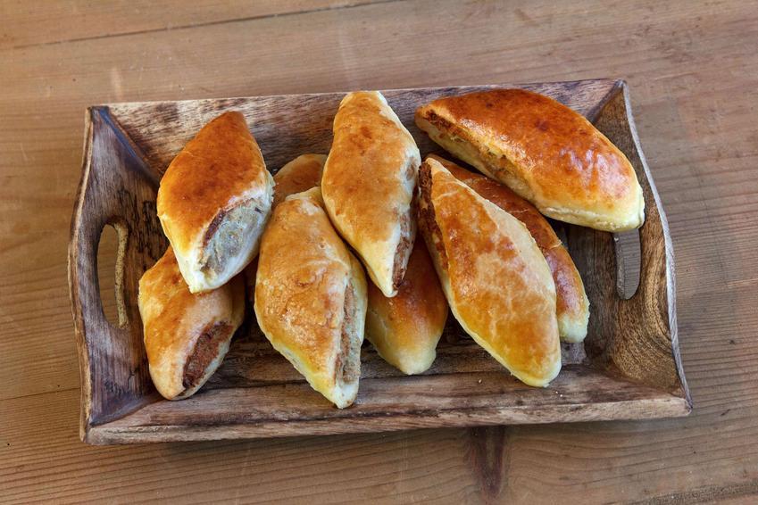 Paszteciki z mięsem podane na drewnianej podkładce.