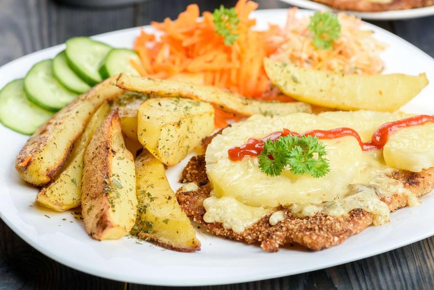 Kotlet po hawajsku podany z pieczonymi ziemniakami i świeżymi warzywami. Całość znajduje się na białym talerzu.