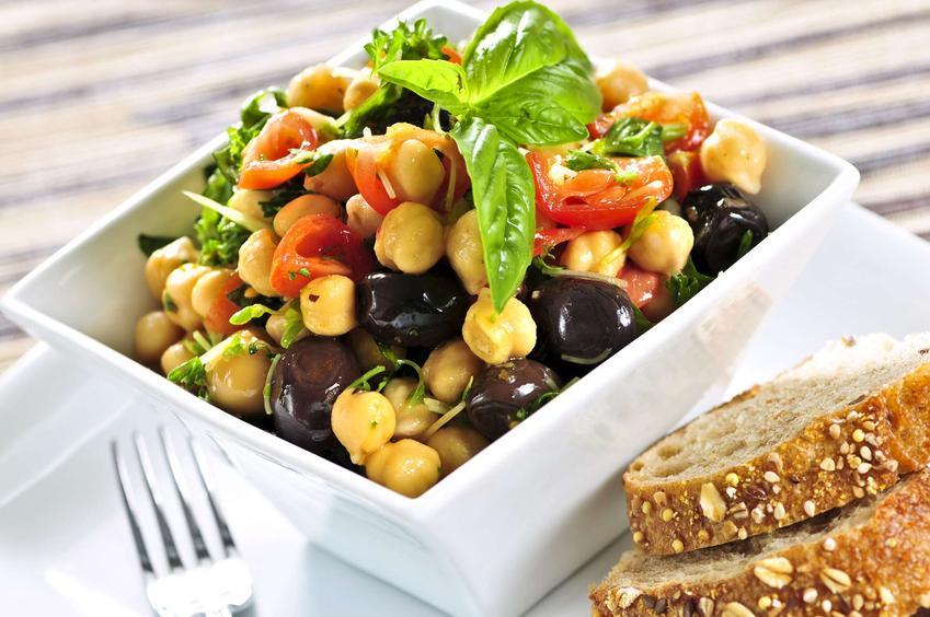 Sałatka z ciecierzycą podana w białej salaterce. Przed nią znajduje się pieczywo.