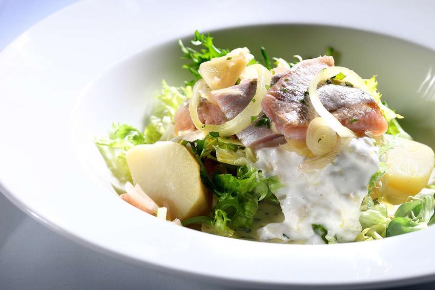 Sałatka śledziowa z ziemniakami podana w białej, głębokiej misce.