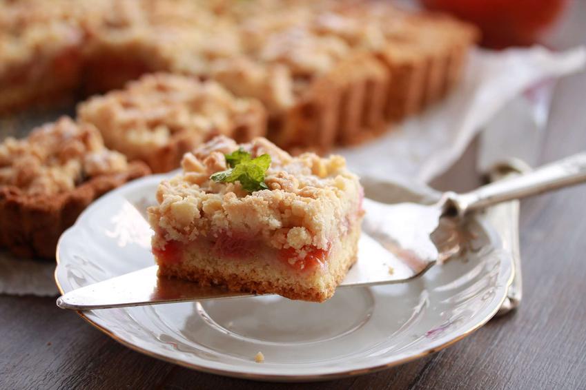 Kawałek kruchego ciasta z rabarbarem na łopatce do ciasta, która leży na porcelanowym talerzyku. W tle widoczna jest reszta ciasta z rabarbarem, leżąca na papierze do pieczenia.
