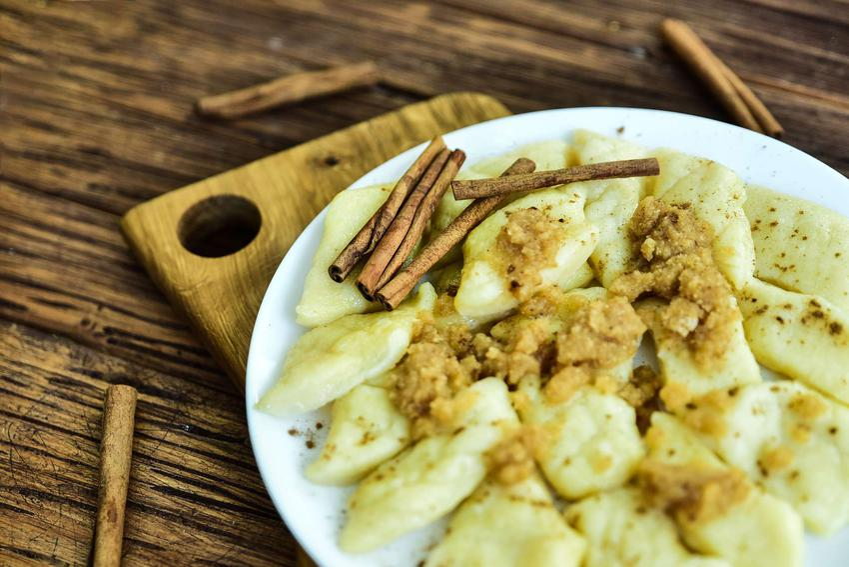 Kluski leniwe podane na talerzu z masłem i cynamonem.