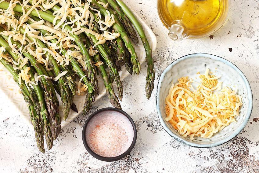 Szparagi zielone z przysmażoną bułką tartą oraz żółtym serem znajdują się na dużym białym talerzu. Obok znajdują się: miseczka z bułką tartą i serem, miseczka z solą oraz buteleczka z oliwą.