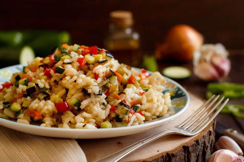 Risotto z warzywami znajduje się na kolorowym talerzu. Obok leży widelec. Talerz stoi na drewnianej podkładce. W tle widać czosnek, zieloną paprykę, buteleczkę z oliwą.