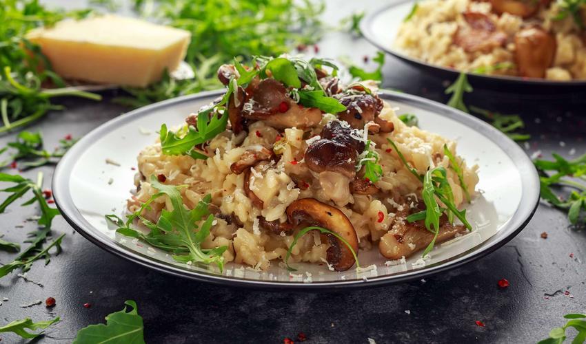 Risotto z grzybami, rukolą i parmezanem znajduje się w białym talerzu. Dookoła porozrzucana jest rukola. W tle widać parmezan w kostce oraz drugą porcję risotto.