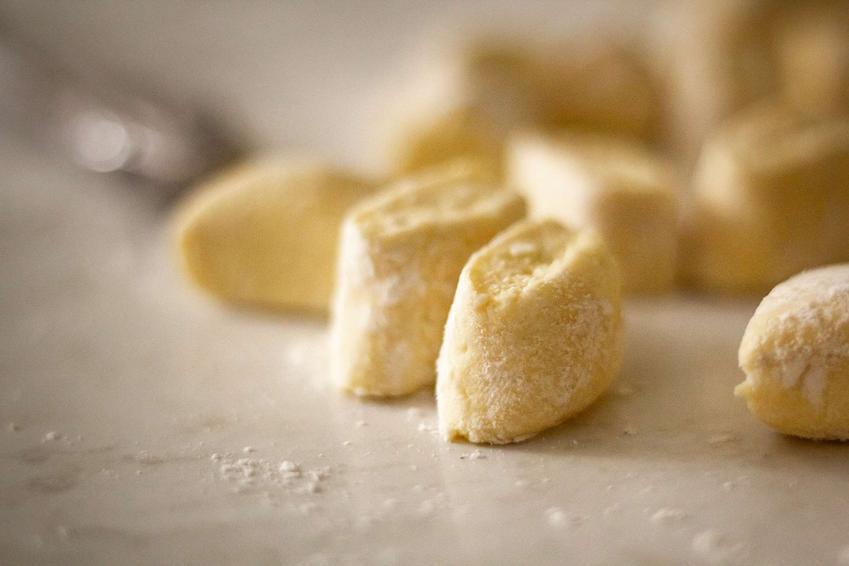 Kopytka z serem oprószone mąką znajdują się na jasnym blacie. Obok leży nóż.