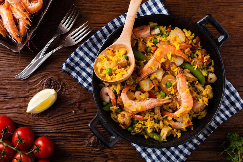 Paella znajduje się w garnku. Obok leżą pomidory, kawałek cytryny, widelce i krewetki.