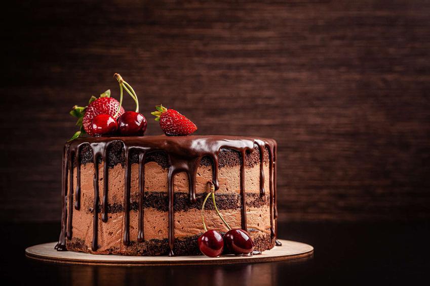 Tort czekoladowy znajduje się na podkładce. Tort udekorowany jest wiśniami i truskawkami.