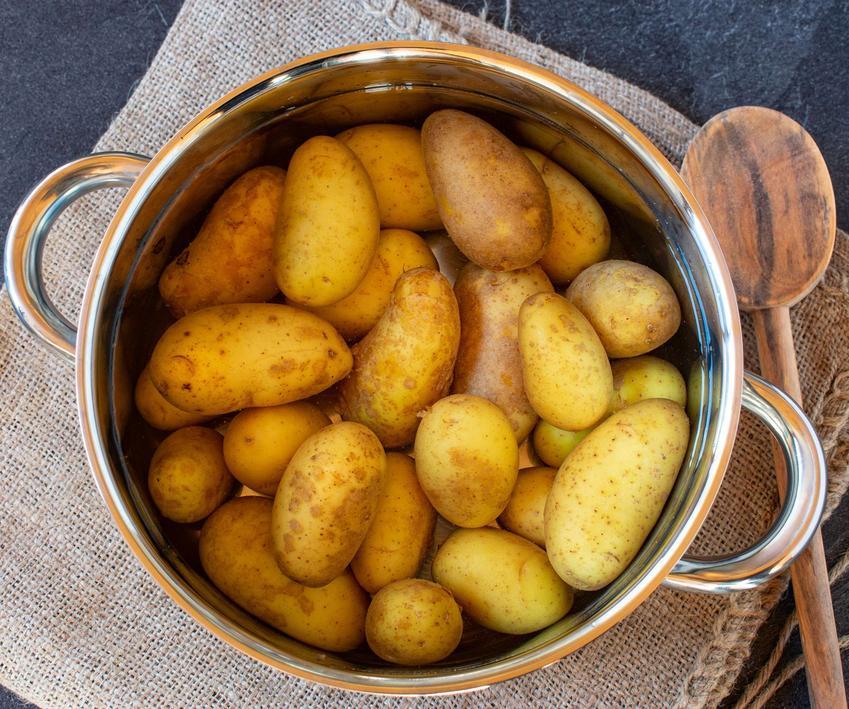 Ziemniaki w mundurkach znajdują się w garnku z wodą. Obok garnka leży drewniana łyżka.