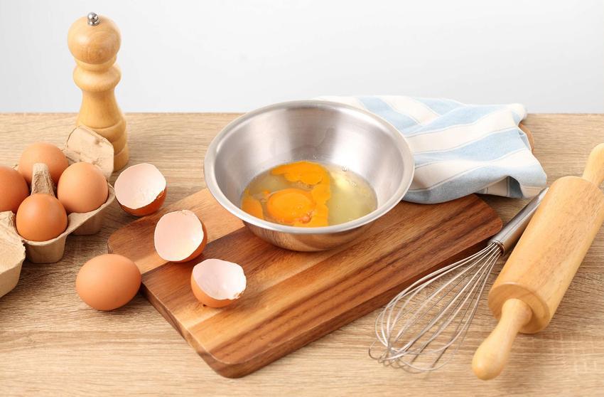 Jajka wbite do srebrnej miski, obok trzepaczka i drewniany wałek.