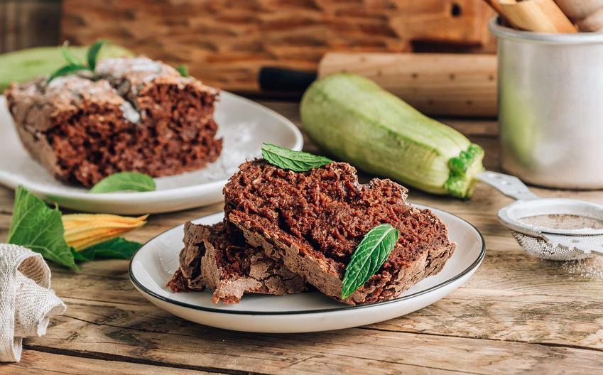Ciasto z cukinii podane na białym talerzu na drewnianym stole, przyozdobione listkami mięty.