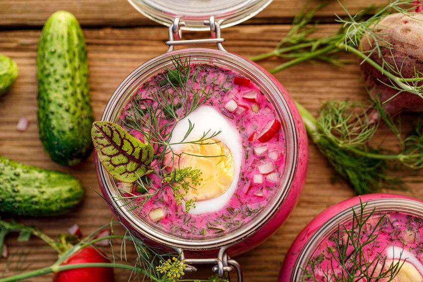 Chłodnik z botwiny w słoiku z połówką jajka. Obok słoika leżą warzywa: burak, ogórki, rzodkiewka i koperek