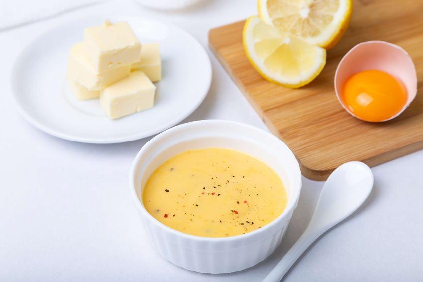Sos holenderski podany w sosjerce z cytryną i żółtkami w tle.