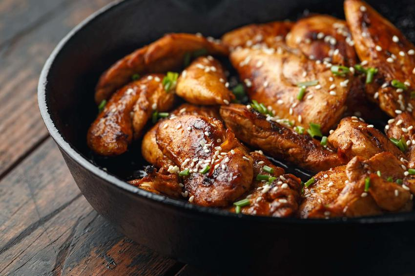 Kurczak teriyaki znajduje się w czarnej wysokiej misce.