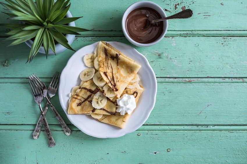 Naleśniki z mąki jaglanej polane sosem czekoladowym i bananem znajdują się na talerzyku, który leży na zielonym stole. Na drugim planie znajduje się miseczka z sosem czekoladowym, kwiatek oraz sztućce.