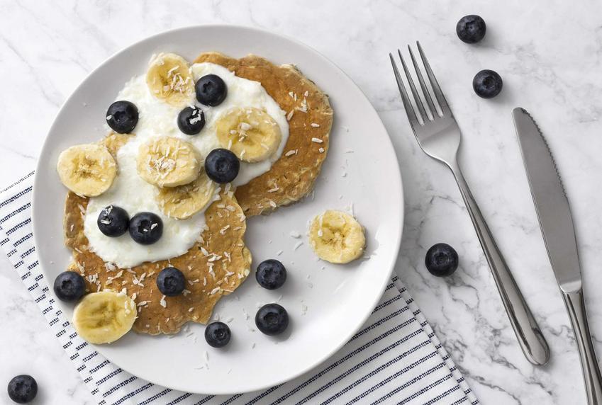 Placki z bananami podane na talerzu. Ozdobione są borówkami, kawałkami bananów oraz jogurtem naturalnym.