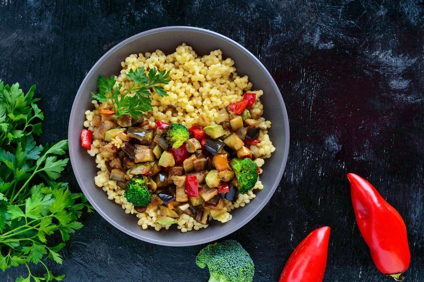 Kasza z warzywami podana w wysokim, szarym talerzu. Dookoła niego leży natka pietruszki, brokuł oraz papryka.