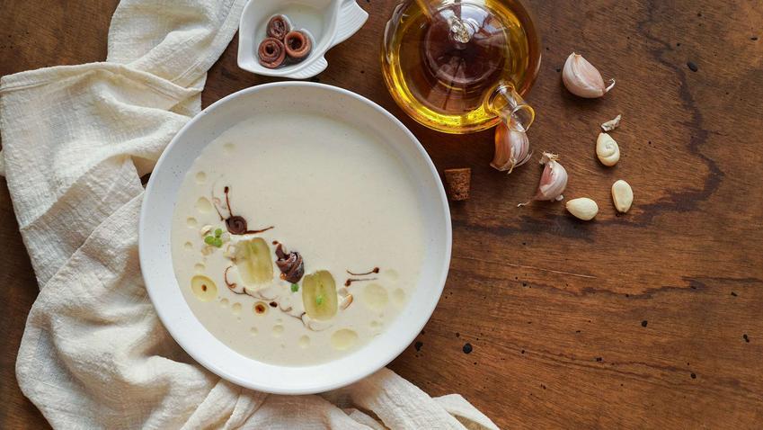Zupa czosnkowa podana w eleganckiej miseczce, udekorowana pokrojonym czosnkiem.