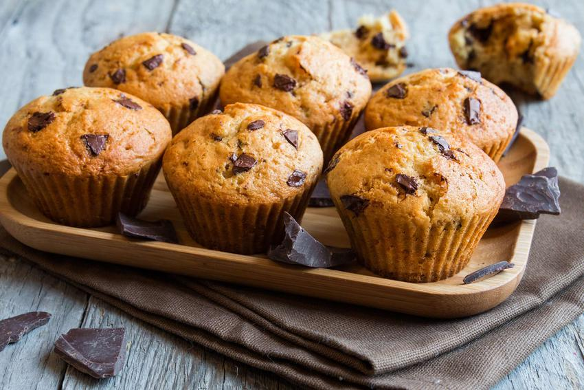 Muffinki z kawałkami czekolady znajdują się na drewnianej podstawce. Dookoła leżą kawałki czekolady.