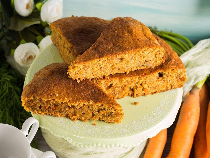 Ciasto marchewkowe pokrojone w kawałki ułożone jest na paterze. W tle ułożona jest marchewka, w rogu można dostrzec kawałek filiżanki.