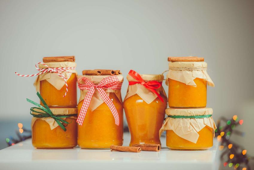 Dżem z dyni i pomarańczy znajduje się w słoiczkach. Obok i na słoikach porozkładane są laski cynamonu.
