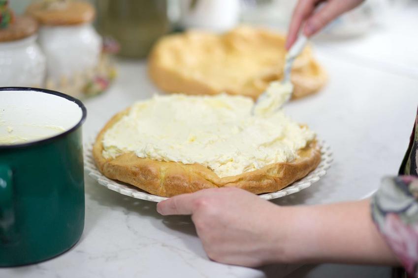 Krem karpatkowy jest rozsmarowywany po cieście parzonym przez kucharza. W tle widać drugi blat karpatki.