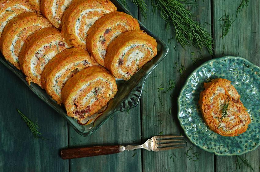 Rolada marchewkowa z serkiem i łososiem wędzonym ułożona na paterze oraz talerzyku. Wszystko znajduje się na zielonym stole na którym leży widelec.